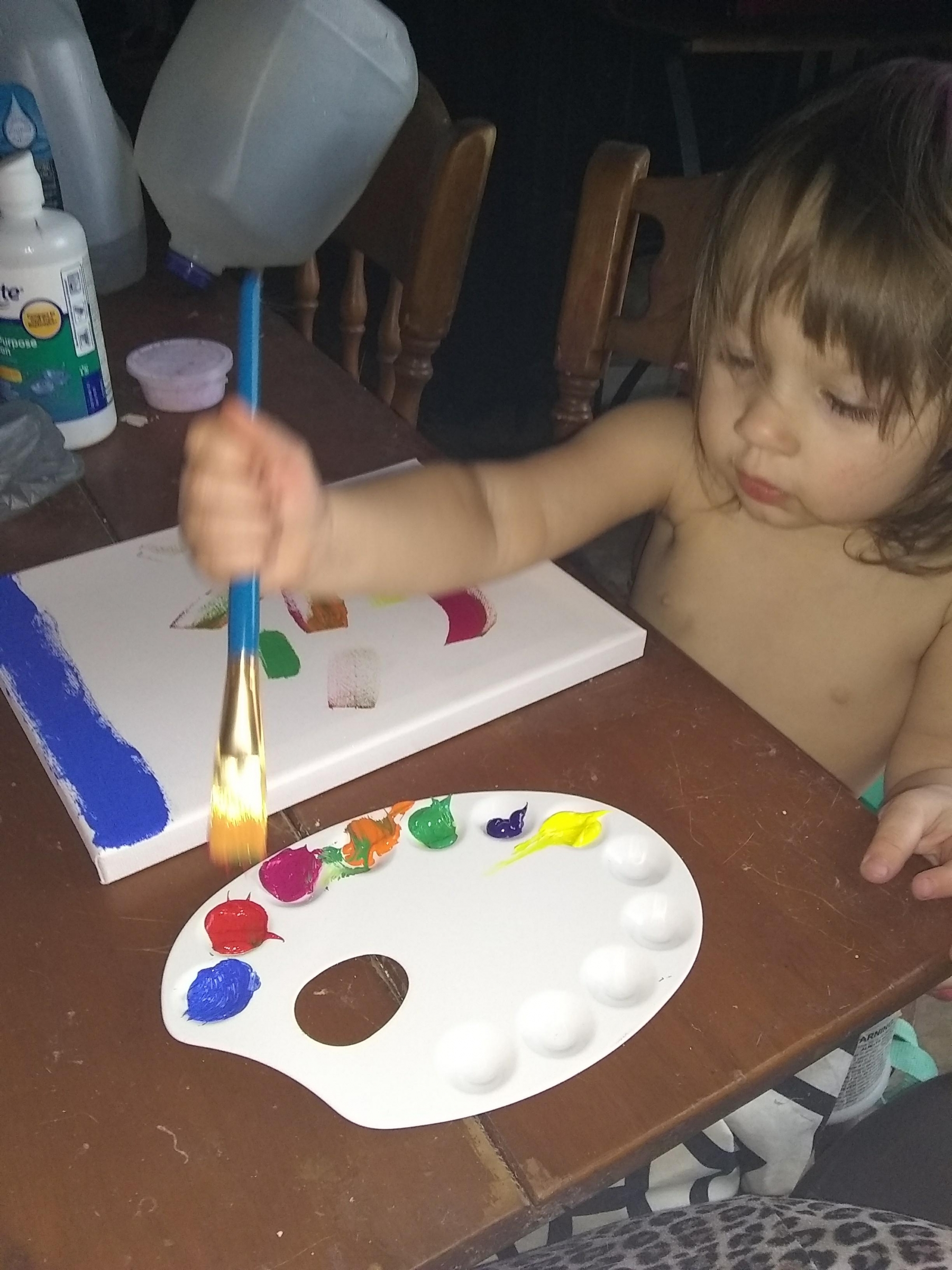 kid painting on canvas using oil painting set bought on amazon