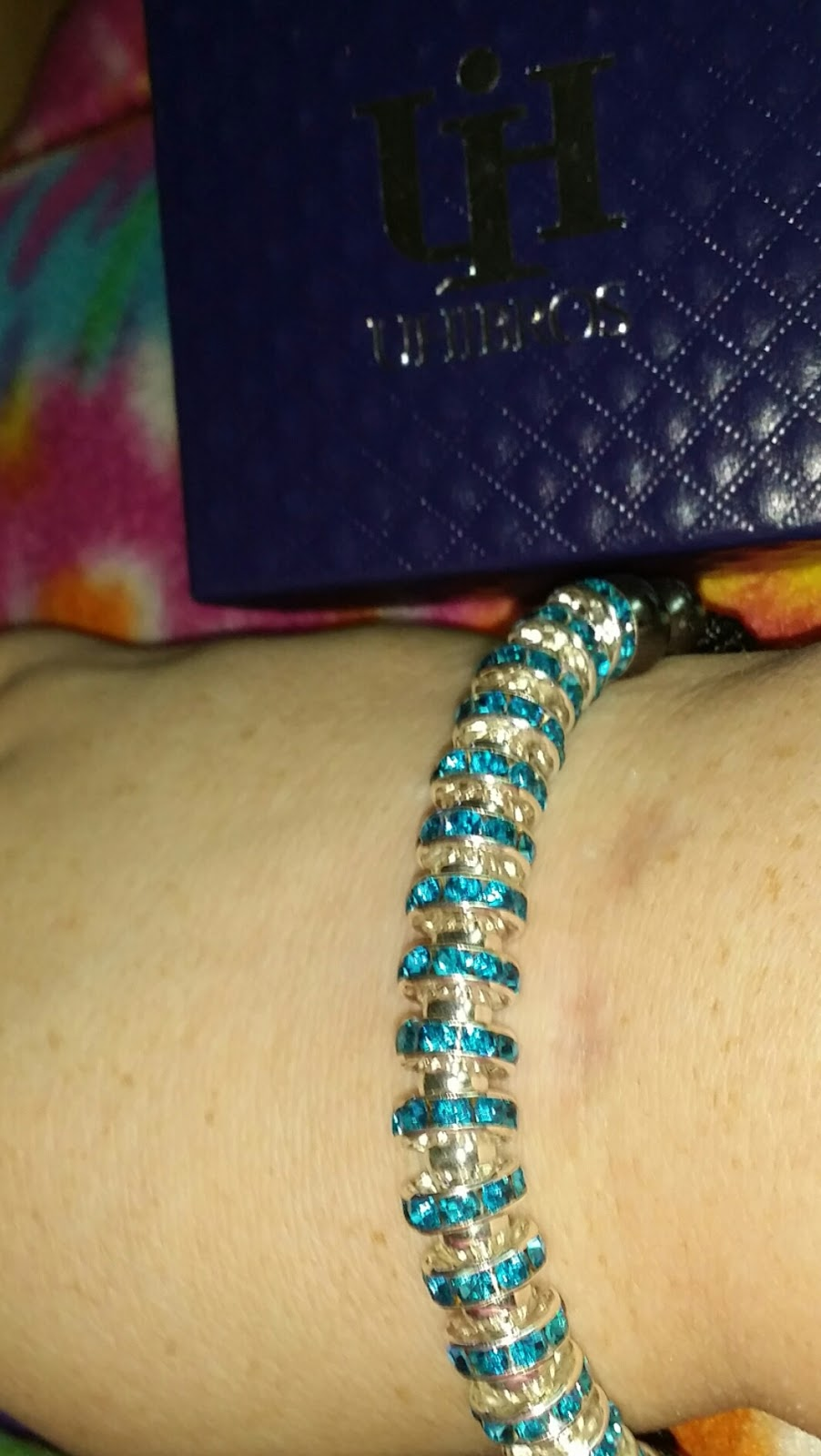 A lovely bracelet with 18 blue Crystal Zircon stoppers, metal alloy spacers, and an adjustable twisted mesh braiding.